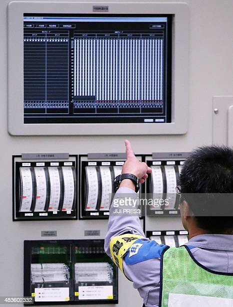 An operator checks the restart of the nuclear reactor at the central control room of the Kyushu Electric Power Sendai nuclear power plant in...