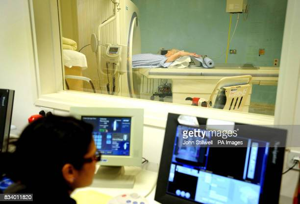 An operator monitors a patient's progress as she is sent through a CT Scanner at University College Hospital in central London The Scanner can detect...