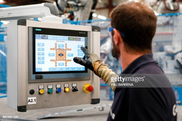 An operator points on a smart touchable screen to control an articulated industrial robot at the Gestamp Automocion factory branch in Abrera near...