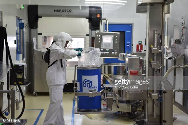 An operator takes the active ingredient out of a barrel ahead of its processing into medicine on the premises of the French pharmaceutical company...