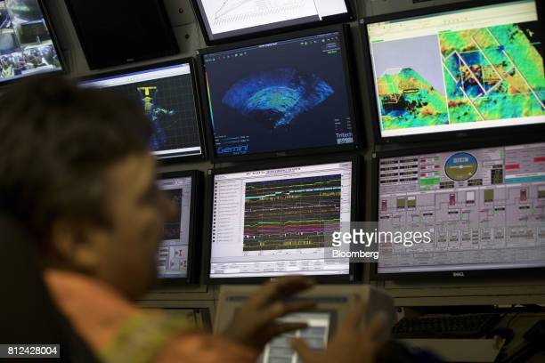 An operator watches screens showing radar scans maps and camera images in the control room as the 'crawler' machine sucks up sediment from the seabed...