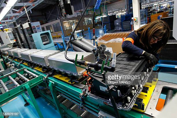 An operator works on the batteries of a Renault Twizy electric car on April 03 2012 in Valladolid The Renault Twizy electric car manufactured...