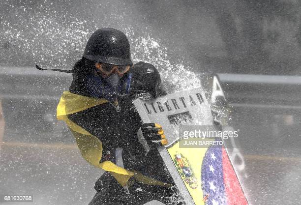 TOPSHOT An oposition demonstrators is hit by the jet from a riot police water cannon during a protest against President Nicolas Maduro in Caracas on...