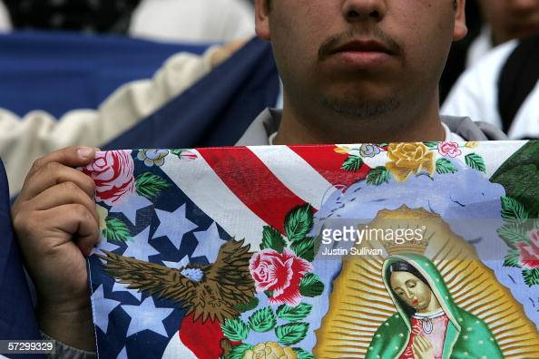 An opponent of house bill HR4437 holds a flag depicting the US colors and the Virgin Mary during a rally protesting immigration reform measures on...