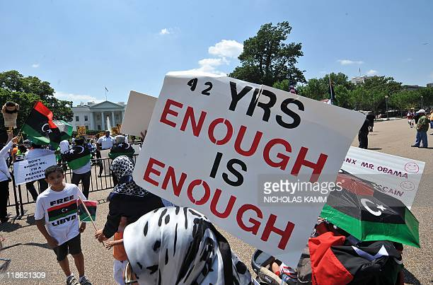An opponent of Libyan leader Moamer Kadhafi holds a sign in front of the White House in Washington on July 9 2011 during opposing demonstrations...