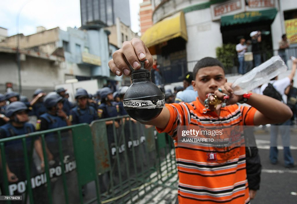 An opponent of Venezuelan president Hugo Chavez holds a tear gas device during a demonstration 23 January, 2008 in Caracas. The Venezuelan government commemorated today the 50th anniversary of the fall of the last dictatorship -gen. Marcos P?rez Jim?nez (1948-58). AFP PHOTO/Juan BARRETO