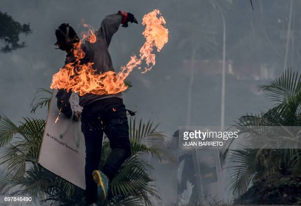 TOPSHOT An opposition activist clashes with riot police during a demonstration against the government of President Nicolas Maduro along the Francisco...