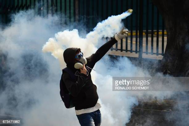 An opposition activist clashes with riot police during a protest march in Caracas on April 26 2017 Protesters in Venezuela plan a highrisk march...