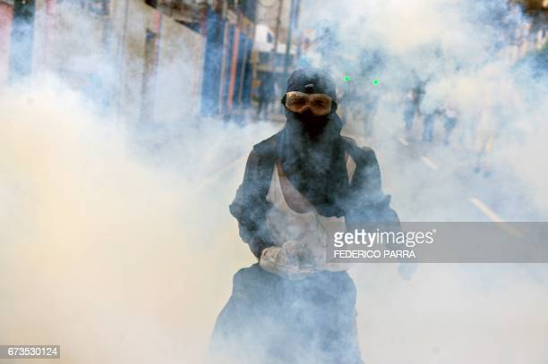 TOPSHOT An opposition activist clashes with riot police during a protest march against President Nicolas Maduro in Caracas on April 26 2017...