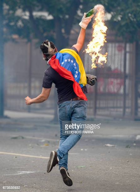 TOPSHOT An opposition activist clashes with riot police during a protest against President Nicolas Maduro in Caracas on April 26 2017 Venezuelan riot...