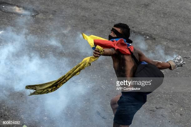 TOPSHOT An opposition activist clashes with the police at the Francisco de Miranda air force base during a demonstration against the government of...