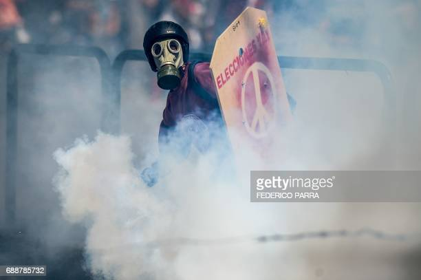 An opposition activist clashes with the riot police during a demonstration against Venezuelan President Nicolas Maduro in Caracas on May 26 2017 Riot...