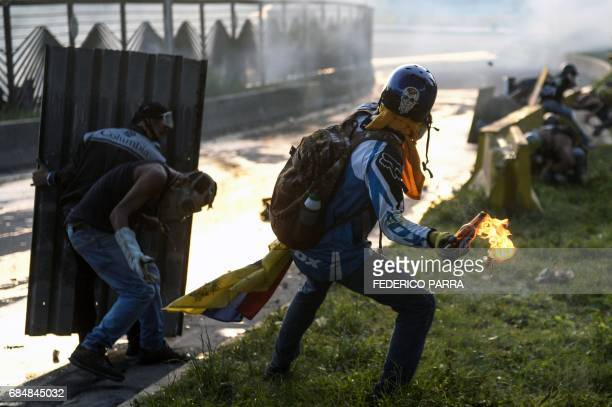 An opposition activist gets ready to throw a Molotov cocktail at riot police in clashes during a protest against President Nicolas Maduro in Caracas...