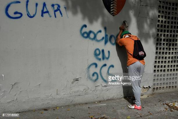 An opposition activist is overwhelm by tear gas during clashes in Caracas on July 10 2017 Venezuela hit its 100th day of antigovernment protests...