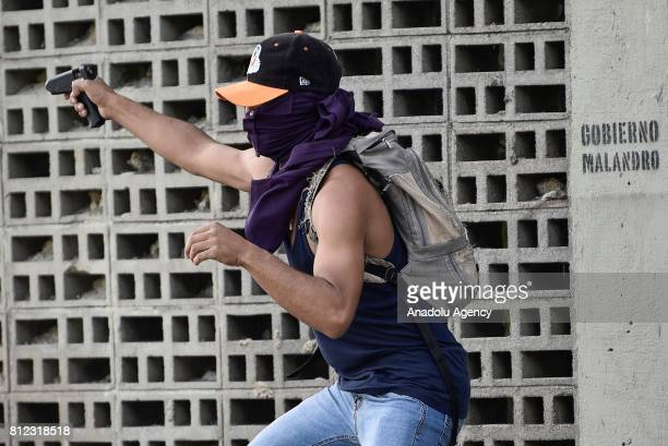 An opposition activist points a hot glue gun towards the National Guard during clashes in Caracas on July 10 2017 Venezuela hit its 100th day of...