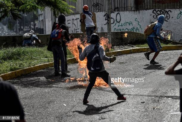 An opposition activist scapes from a molotov cocktail during clashes in Caracas on July 10 2017 Venezuela hit its 100th day of antigovernment...