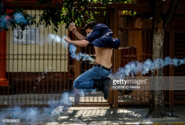 TOPSHOT An opposition activist thows a stone at riot police during clashes following a protest against President Nicolas Maduro in Caracas on April...