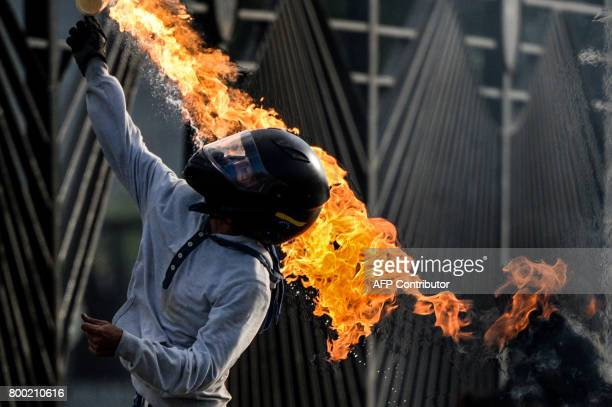 TOPSHOT An opposition activist throws a molotov cocktail as demonstrators blocking a highway in Caracas clash with police during a protest against...