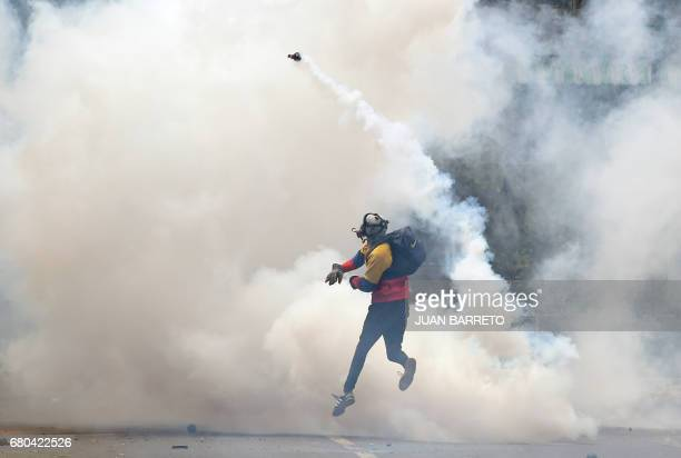 TOPSHOT An opposition activist throws back tear gas to the police as clashes erupt during a protest against President Nicolas Maduro in Caracas on...