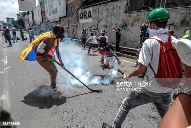 An opposition activist uses a hockey stick to hit at tear gas grenades in a clash with riot police during a demostration against Venezuelan President...