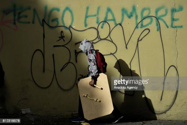 An opposition activist walks in front of a wall depicting the phrase 'Im Hungry' during clashes in Caracas on July 10 2017 Venezuela hit its 100th...