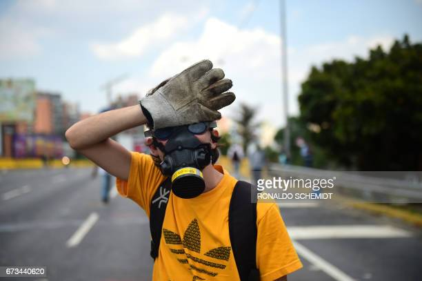 An opposition activist wearing a gas mask and a protective glove on his right hand participates in a protest march in Caracas on April 26 2017...
