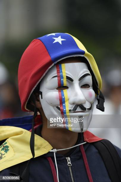 An opposition activist wears a Guy Fawkes mask as he marches towards the Supreme Court of Justice in Caracas in an offensive against President Maduro...