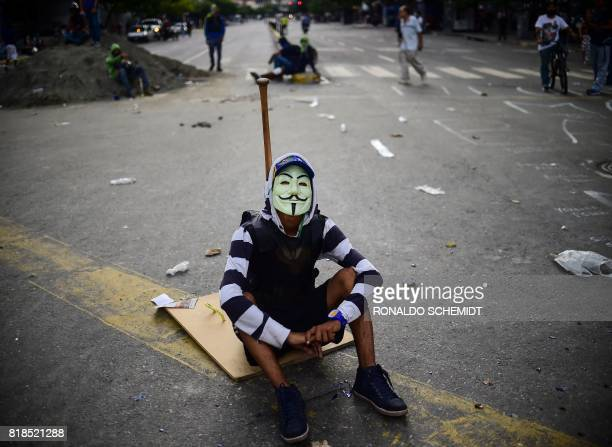 An opposition activist wears a Guy Fawkes mask during a blockade to protest against Venezuelan President Nicolas Maduro in Caracas on July 18 2017...