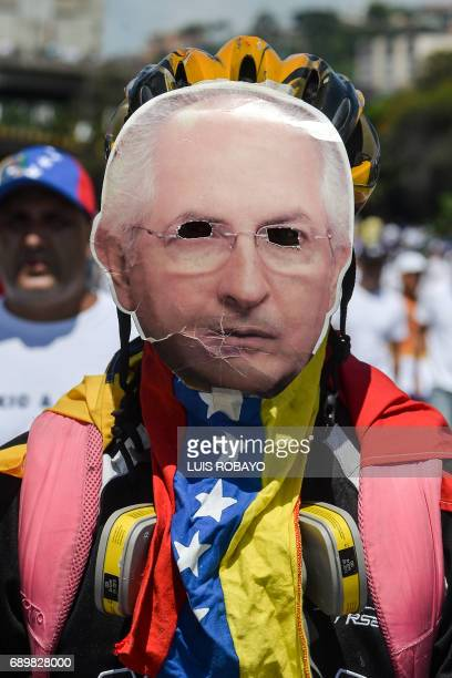 An opposition activist wears a mask of the mayor of Metropolitan Caracas Antonio Ledesma during a demonstration against President Nicolas Maduro's...