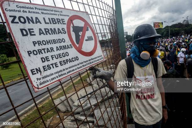 An opposition activists standing next to a sign reading 'firearms free zone' demonstrates against the government of Venezuelan President Nicolas...
