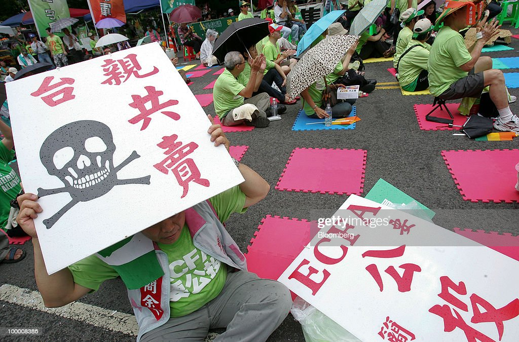 An opposition Democratic Progressive Party (DPP) supporter holds placards at a sit-in protest in Taipei, Taiwan, on Thursday, May 20, 2010. President Ma Ying-jeou has pushed for the trade agreement with China to prevent Taiwan from being 'marginalized' after a Chinese accord with the 10-member Association of Southeast Asian Nations took effect this year. The proposal sparked opposition demonstrations amid concern China may boost its influence over Taiwan. Photographer: Maurice Tsai/Bloomberg via Getty Images