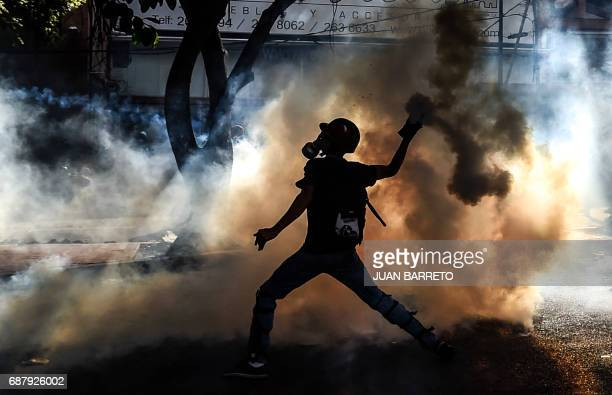 TOPSHOT An opposition demonstrator clashes with riot police in Caracas on May 24 2017 Venezuela's President Nicolas Maduro formally launched moves to...