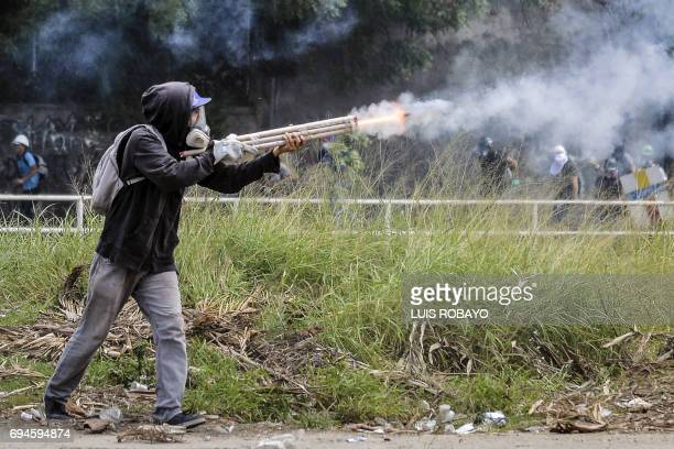 TOPSHOT An opposition demonstrator fires an improvised weapon in a clash with riot police during the 'Towards Victory' protest against the government...
