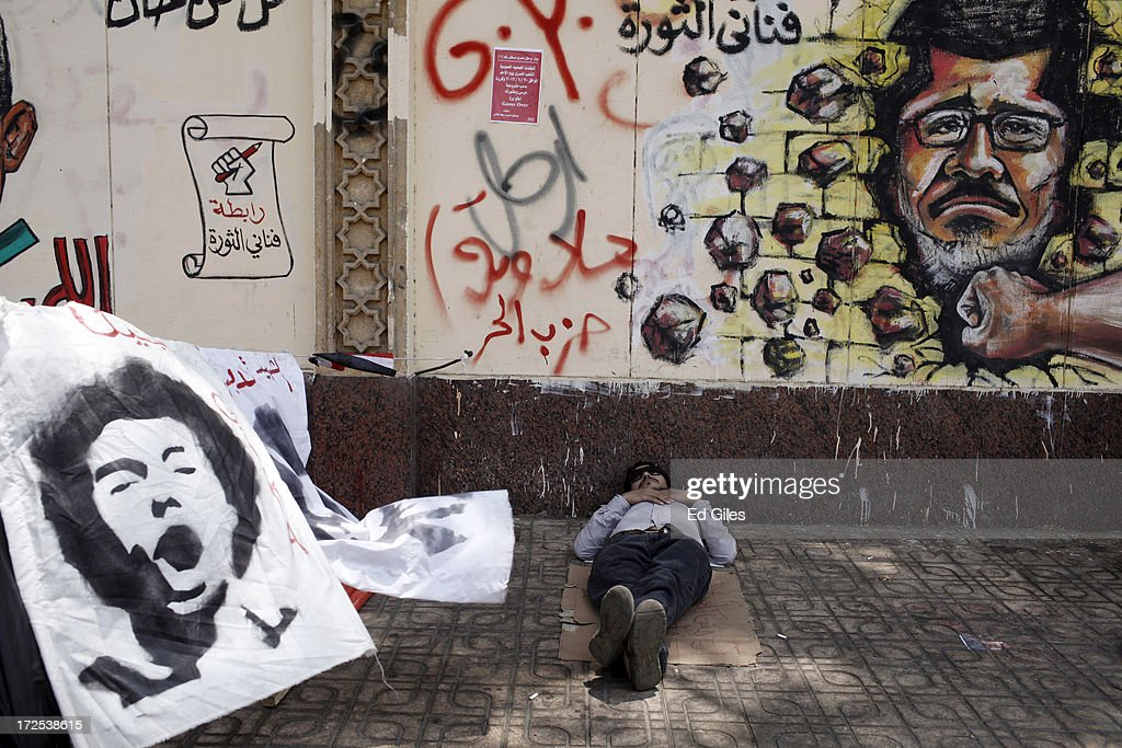 An opposition demonstrator sits below graffiti of Egyptian President Mohammed Morsi on the walls of Egypt's Presidential Palace in the suburb of Heliopolis on July 3 2013, in Cairo, Egypt. The Egyptian Health Ministry reported at least 16 people were killed overnight on July 2 in violent clashes between Pro-Morsi and Anti-Morsi protesters in the Cairo suburb of Giza. An Army ultimatum to President Morsi comes to an end on Wednesday afternoon. In a statement on July 1, the Egyptian Army asked Egyptian President Mohammed Morsi to resolve mass demonstrations against his continued rule or face intervention by the military within 48 hours, after millions of Egyptians took to the streets to protest Morsi's rule on June 30. (Photo by Ed Giles/Getty Images).