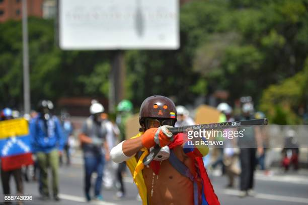 An opposition demonstrator 'takes aim' with a hockey stick at riot police during clashes in Caracas on May 26 2017 Both the Venezuelan government and...