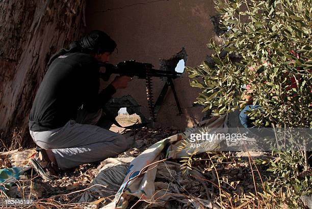An opposition fighter aims fire through a hole in the wall as he holds a position during clashes with government forces in the northern rebelheld...