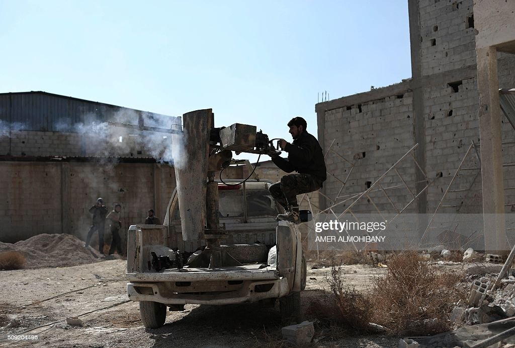 An opposition fighter fires a machine gun in Tal al-Aswan in the area of the eastern Ghouta rebel bastion east of the Syrian capital, Damascus, during clashes with government forces on February 9, 2016. / AFP / AMER ALMOHIBANY