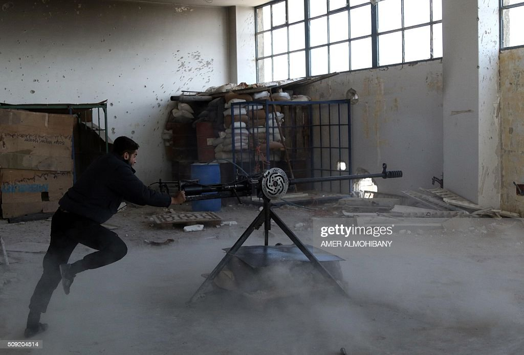 An opposition fighter fires a mcahine gun in Tal al-Aswan in the area of the eastern Ghouta rebel bastion east of the Syrian capital, Damascus, during clashes with government forces on February 9, 2016. / AFP / AMER ALMOHIBANY