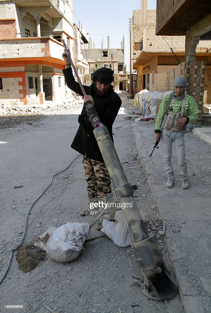 An opposition fighter from the Al-Ikhlas brigade prepares a home-made rocket in Syria's northeastern city of Deir Ezzor on October 9, 2013. The Syrian Observatory for Human Rights reported fierce fighting in Damascus province between rebels and troops backed by pro-regime militias and fighters from Lebanon's Shiite Muslim movement Hezbollah.