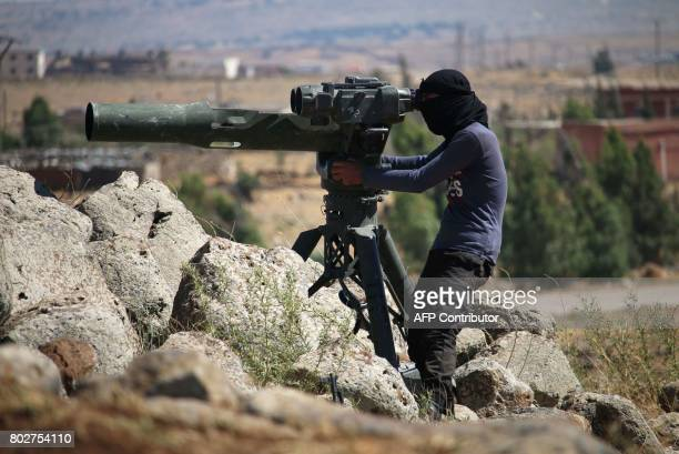 An opposition fighter looks for government forces' positions in Syria's southwestern Quneitra province on June 28 2017 during ongoing clashes for...