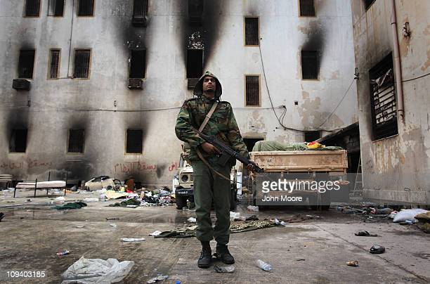 An opposition militiaman stands guard in front of the charred national security building on February 24 2011 in Benghazi Libya The building was...