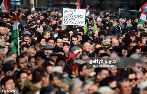 An opposition party participant lifts his placard up reading 'No for usury yes for a government of laws' during the speech of the Hungarian Prime...