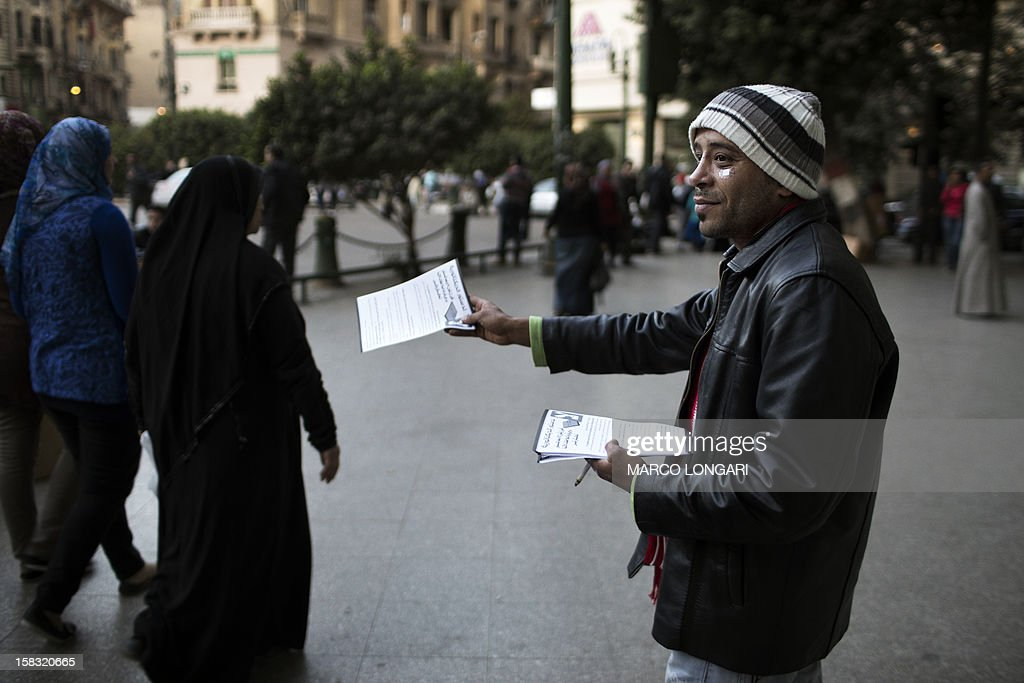 An opposition supporter distributes flyers encouraging Egyptians to vote against the new consitution in down town Cairo on December 13, 2012. The political struggle over a divisive new constitution for Egypt went into campaign mode with Islamists backing President Mohamed Morsi and the opposition urging either support or rejection of the draft charter.