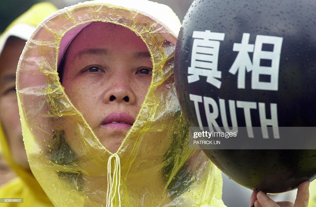 An opposition supporter holds a balloon with a protest slogan during a protest rally in Taipei, 20 May 2004 as President Chen is sworn in for a second four-year term. The opposition is disputing Chen's re-election claiming it was the result of unfair election. Chen won the 20 March presidential polls by a razor-thin margin of 0.22 percent, or 30,000 votes.