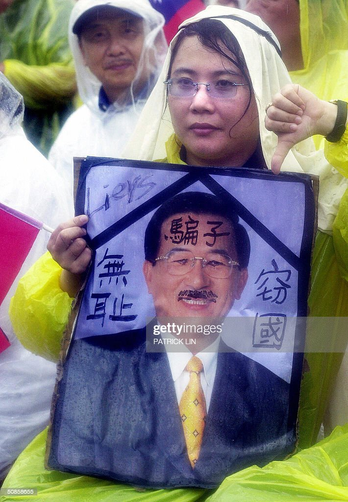 An opposition supporter holds a photo of Taiwanese President Chen Shui-bian and shows a thumb-down during a protest rally in Taipei, 20 May 2004 as President Chen is sworn in for a second four-year term. The protest sloan printed on the photo reads: 'Liar, Shameless, Country stolen'. The opposition is disputing Chen's re-election claiming it was the result of unfair election. Chen won the 20 March presidential polls by a razor-thin margin of 0.22 percent, or 30,000 votes.