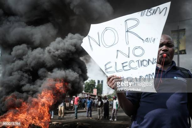 TOPSHOT An opposition supporter holds a placard during their protest against Independent Electoral and Boundaries Commission officials over claims of...