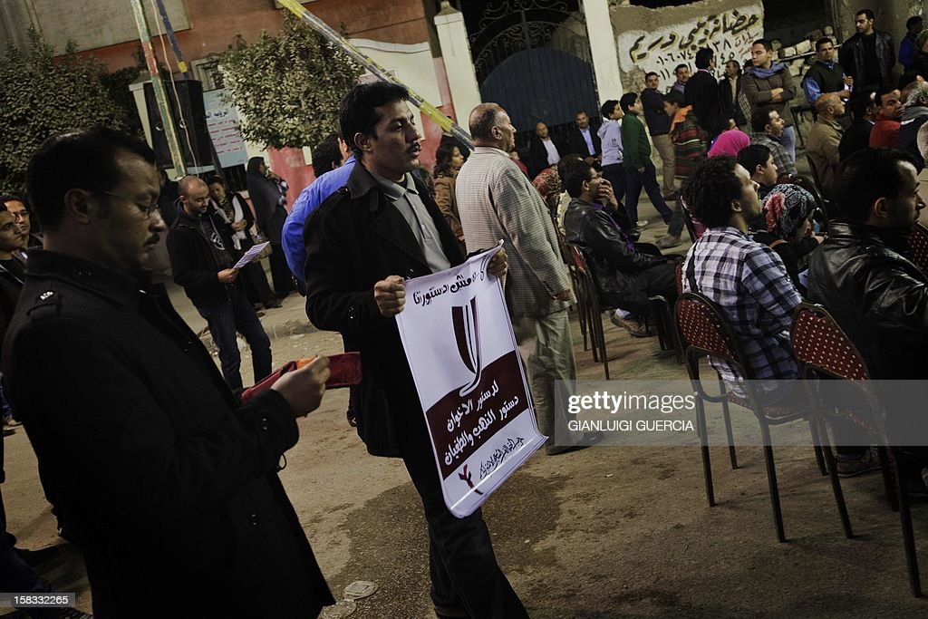 An opposition supporter holds a sign calling people to vote 'no' in a referendum on a draft constitution, on December 13, 2012, at an opposition gathering in Helwan on the outskirts of Cairo. Egypt's crisis showed no sign of easing as the army delayed unity talks meant to ease political divisions and the opposition set near-impossible demands for taking part in a looming constitutional referendum. Voting on the controversial Islamist-backed draft charter is due to start on Saturday with a second round scheduled for a week later. AFP PHOTO/GIANLUIGI GUERCIA