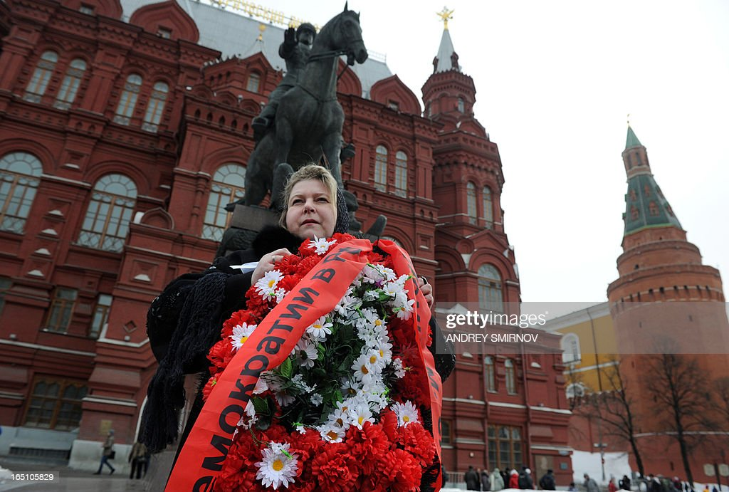An opposition supporter holds a wreath with the inscription 'Democracy' on it during a rally in central Moscow on March 30, 2013. Russian police detained around a dozen anti-Kremlin opposition activists today after they turned up near Red Square for a rally to support their jailed colleagues.