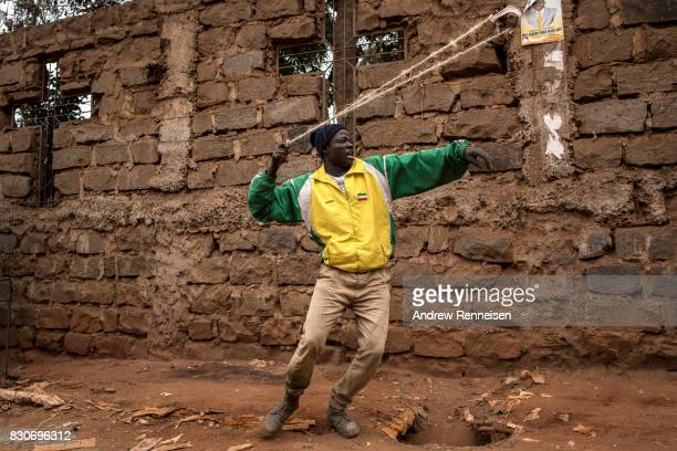 An opposition supporter prepares a slingshot to use against Kenyan police forces as the two sides clashed in the Kibera slum on August 12 2017 in...