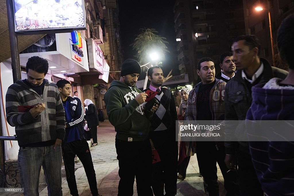 An opposition supporter reads a leaflet calling people to vote 'no' in a referendum on a draft constitution, on December 13, 2012, at an opposition gathering in Helwan on the outskirts of Cairo. Egypt's crisis showed no sign of easing as the army delayed unity talks meant to ease political divisions and the opposition set near-impossible demands for taking part in a looming constitutional referendum. Voting on the controversial Islamist-backed draft charter is due to start on Saturday with a second round scheduled for a week later. AFP PHOTO/GIANLUIGI GUERCIA